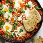 Close up shot of Shakshuka with feta cheese topped with bread slices