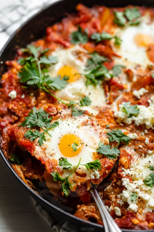 close up of spoon taking a portion out of a skillet of shakshuka
