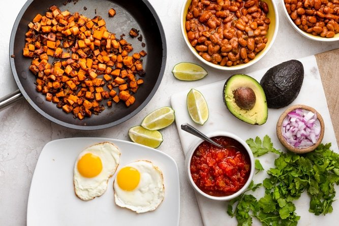 Ingredients to make the recipe: pinto beans, sweet potatoes, fried eggs and Mexican style toppings