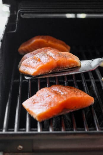 3 Salmon fillets on a grill with spatula under one before flipping it