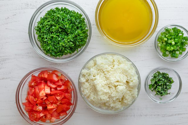 Ingredients to make recipe: grated cauliflower, tomatoes, parsley, olive oil and lemon juice, green onions, mint