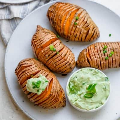 Sweet potatoes on a serving platter with yogurt dip next to it.