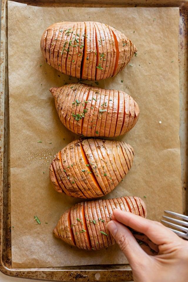 Sweet potatoes halfway through cooking, adding herbs on top