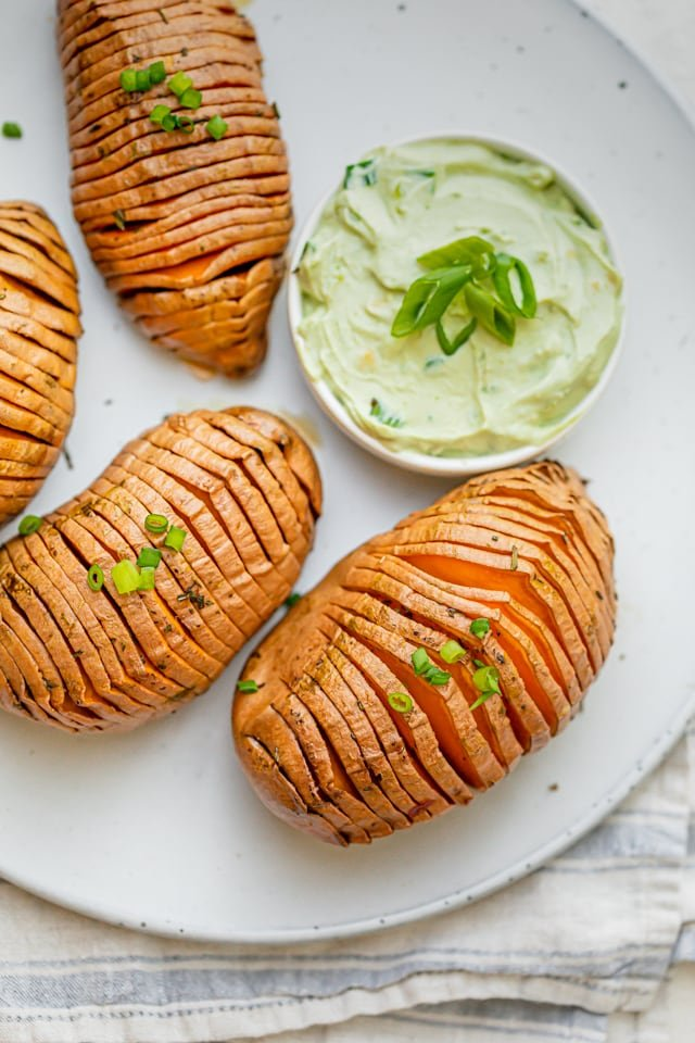 Baked hasselback sweet potatoes on a white plate served with avocado yogurt sauce