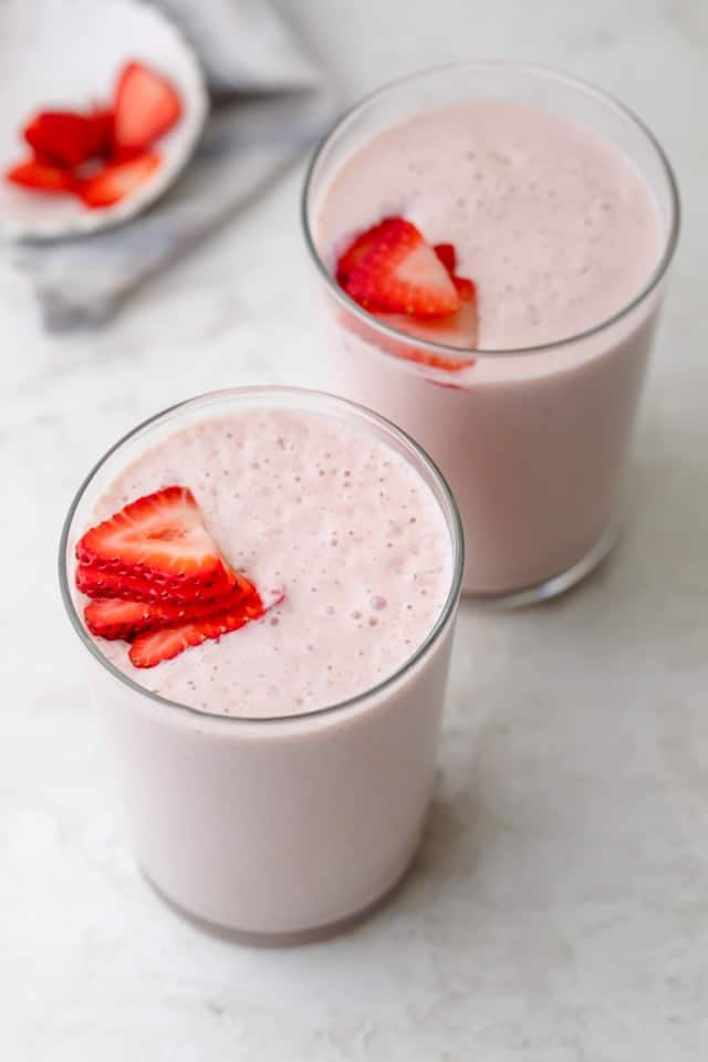 Two glasses of strawberry banana smoothie topped with strawberries