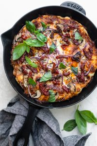 Cast Iron Pizza garnished with basil and sundried tomatoes