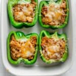 Chicken stuffed peppers in a white baking dish when they come out of oven