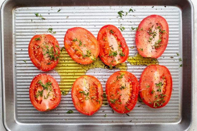 Roma tomatoes on a baking sheet drizzled with olive oil and herbs
