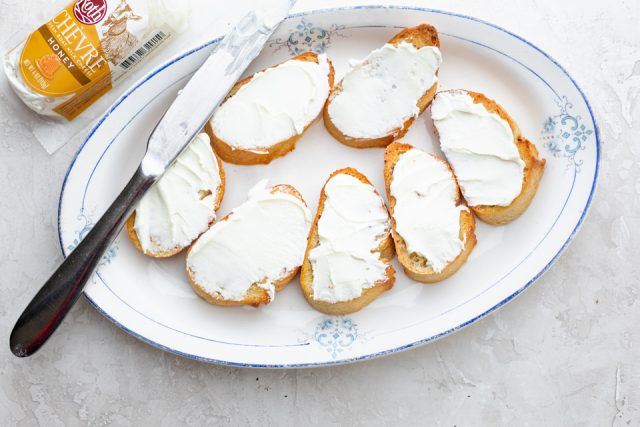 Crostini on a white dish with a table knife for spreading goat cheese