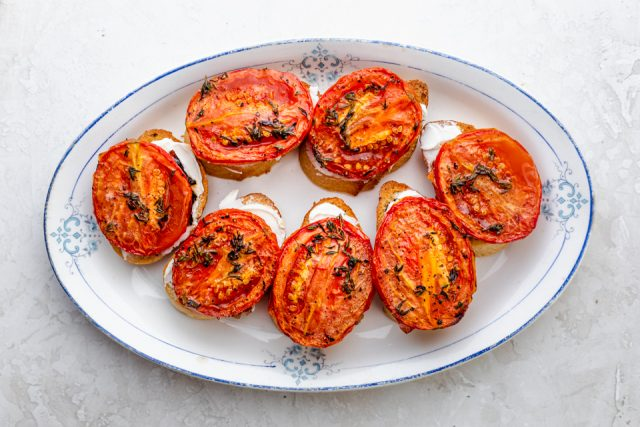 Roasted tomatoes topped on crostini on a white plate