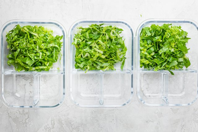 Three clear glass meal prep containers with lettuce