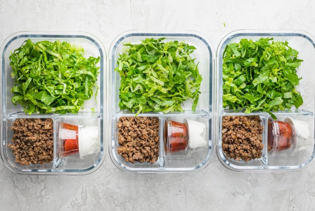 Three clear glass meal prep containers with lettuce, taco beef, and accompaniments getting added