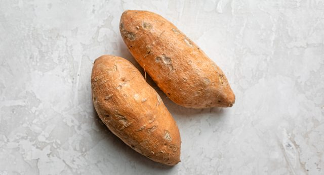 Two medium size sweet potatoes potatoes before peeling and cutting