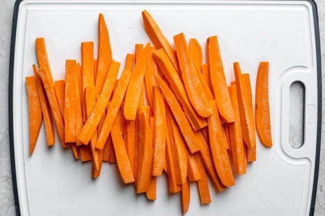 Sliced raw sweet potatoes on a cutting board