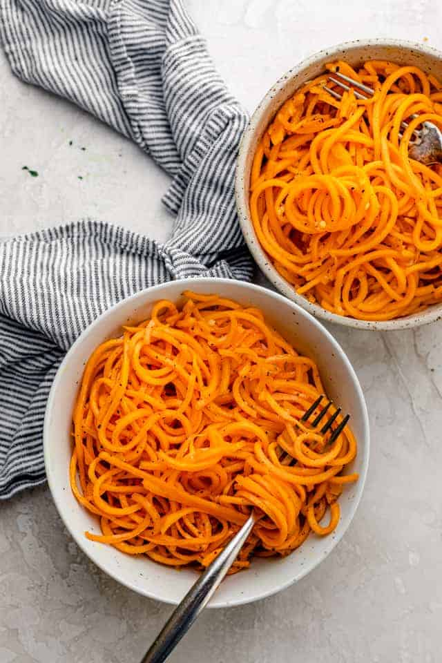 Two bowls of butternut squash noodles with forks inside bowls
