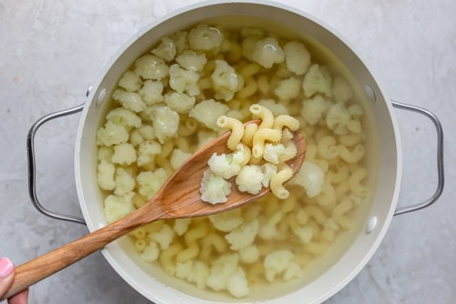 Pot boiling macaroni and cauliflower florets