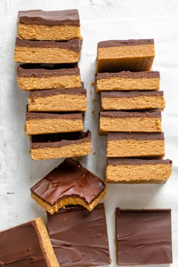 Stack of chocolate peanut butter bars with one bite taken out of one of them