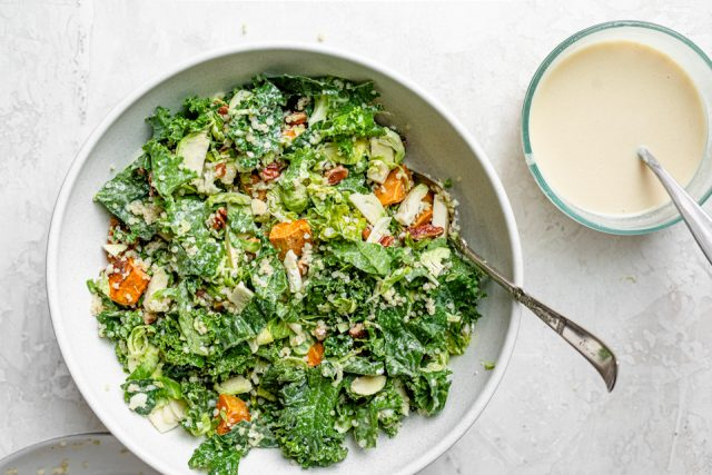 The tossed salad in a large bowl with a side of tahini dressing