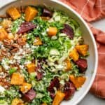 Fall harvest salad in a large bowl with an orange linen towel nearby