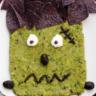 Frankenguac Halloween guacamole decorated with tortilla chips, olive and sour cream