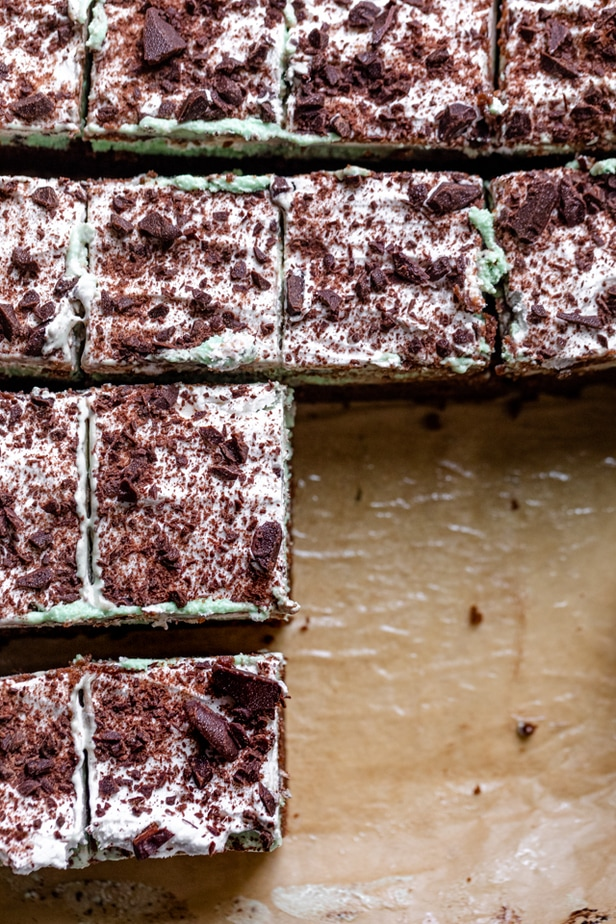Mint chocolate brownies cut up into 16 squares on parchment papper