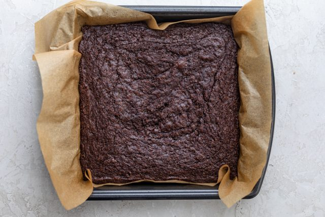 Complete cooled brownie in pan with parchment paper