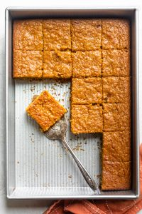Pumpkin bar recipe after being cut in baking pan and slices served