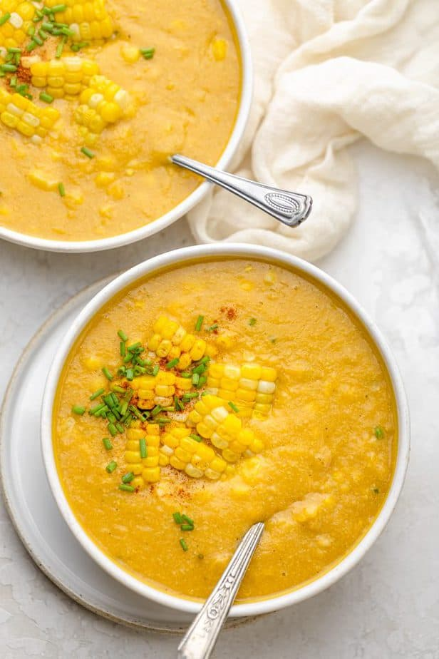 Two bowls of vegan corn chowder with spoons inside