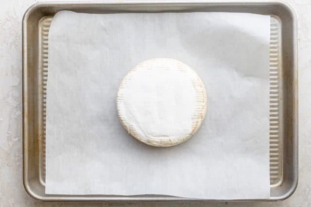 Wheel of triple cream brie before placing in the oven to bake