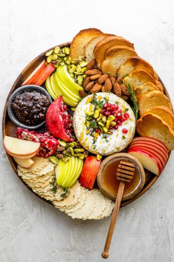Baked Brie recipe on a cheese board with toast, crackers, fruit and accompaniments