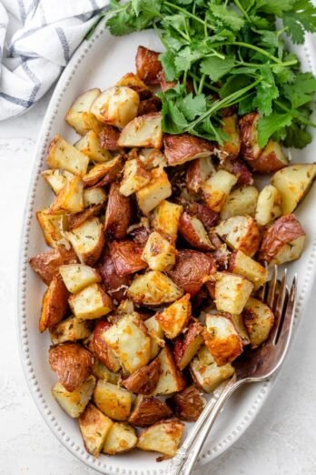 Long serving dish of garlic roasted potatoes served with cilantro