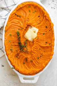 Large oval casserole dish with healthy mashed sweet potatoes topped with butter and thyme