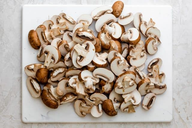 Sliced mushrooms on cutting board before cooking