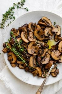 Spoon serving the sauteed mushrooms on a white plate