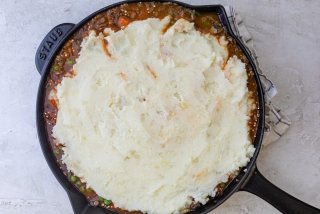 Spreading the potato crust over the pie in the cast iron skillet