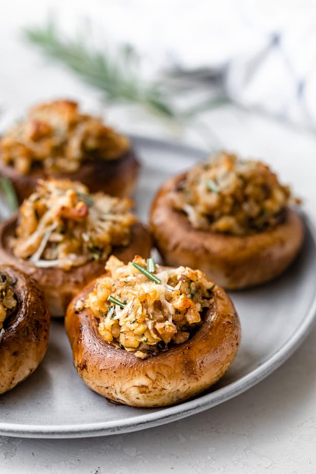 Vegetarian stuffed mushrooms on a dish garnished with rosemary