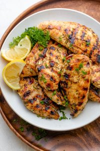 Final grilled chicken tenders served with lemon slices and garnished with parsley