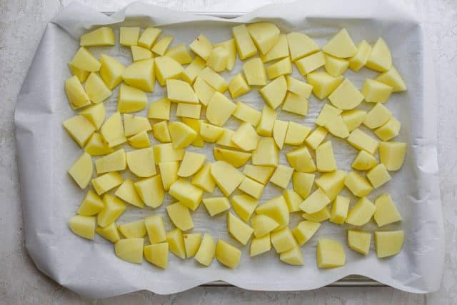 Baking dish with parchment paper and potatoes cut into small cubes