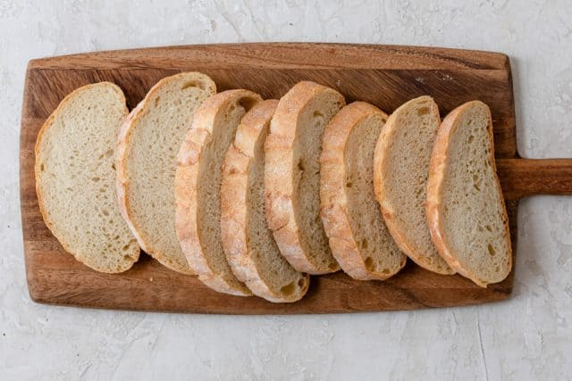 Sliced bread on cutting board ready to make french toast