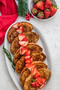 Vegan french toast on a long serving platter with sliced strawberries on top