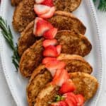 Eggless french toast for a crowd topped with sliced strawberries