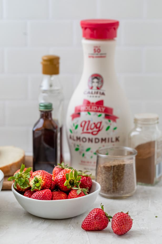 Ingredients to make the recipe along with bowl of strawberries for topping