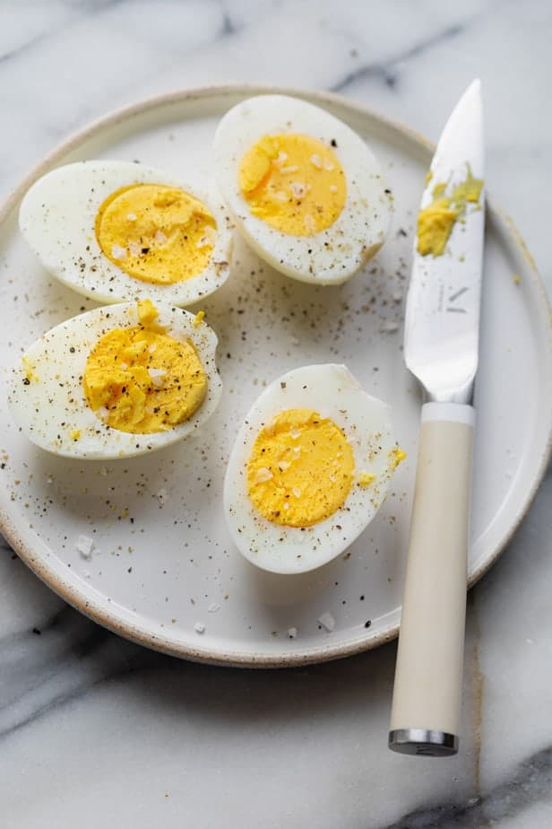 Air Fryer hard boiled eggs sliced in half with salt and pepper