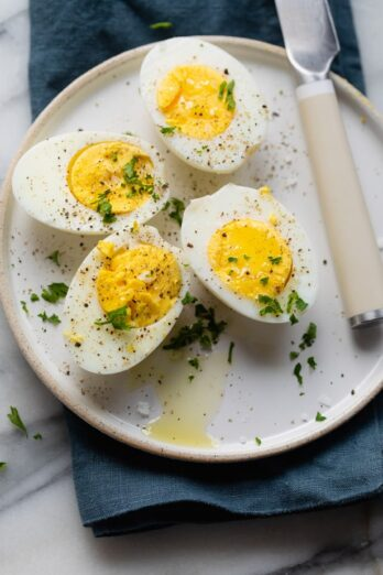 Easy hard boiled eggs made in air fryer cut in half on a white plate