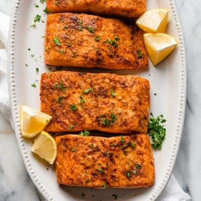 Air Fryer Salmon recipe garnished with lemon wedges and parsley
