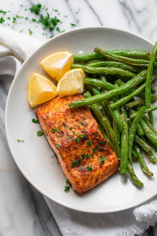 Plate with salmon and green beans with lemon wedges
