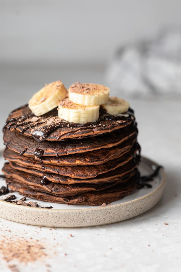 Chocolate protein pancakes topped with sliced bananas and cocoa powder