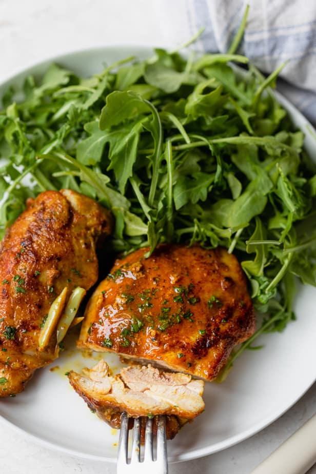 Pan seared chicken thighs served with arugula