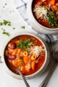 Close up of mug bowl of vegetarian minestrone soup topped with parsley and parmesan cheese