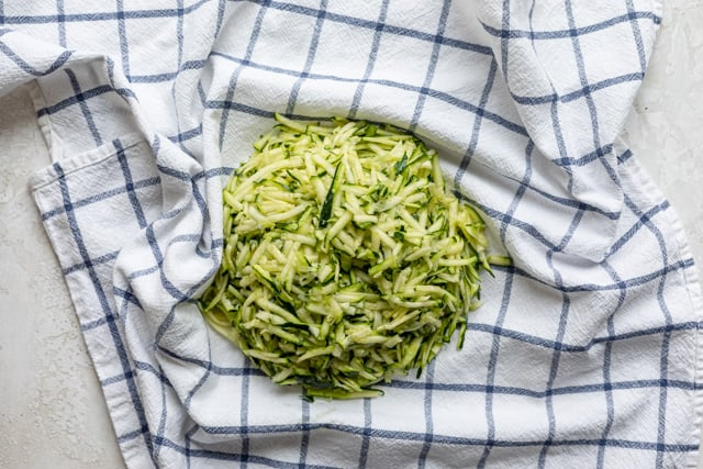 shredded zucchini on a kitchen towel before drying